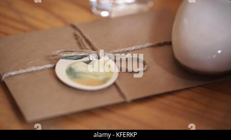 Vintage package tied up with string. Close up envelope sealed. Envelope of kraft paper tied with twine, with a red - Stock Photo