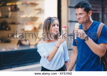 Young couple walking through city and eating ice cream - Stock Photo