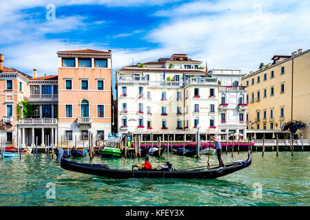 Tourists enjoy a gondola ride on the Grand Canal in Venice, Italy - Stock Photo