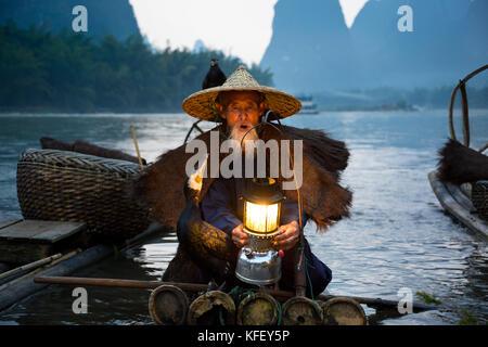 An old fisherman prepares for fishing in a traditional way using hand cormorant in Li River near Xingping, Yangshuo, - Stock Photo