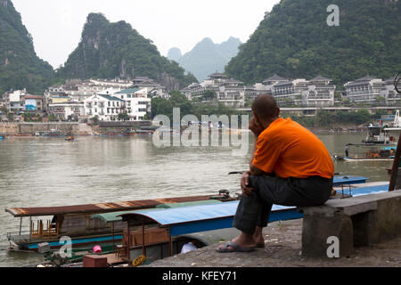 Chinese man looks at Yangshuo city center and Yulong River in Guangxi Zhuang Autonomous Region of China - Stock Photo