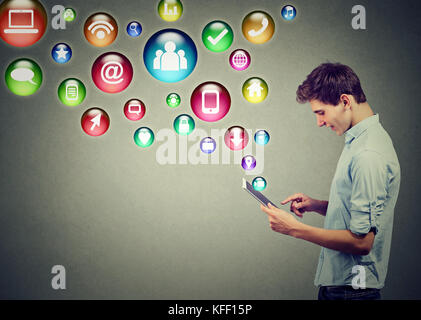 Mobile technology high tech concept. Side profile of a young man using tablet computer with social media application - Stock Photo