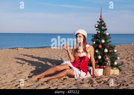Christmas holidays at sea on the beach with a cocktail - Stock Photo