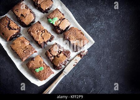 Brownies. Homemade chocolate fudge brownies on rustic black background, top view. - Stock Photo