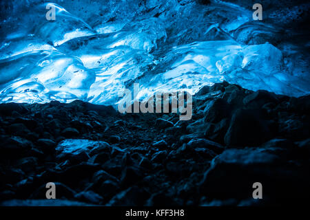 In a narrow tunnel under a glacier in British Columbia, Canada, the ice above glows blue from the sun shining through layers of ice above.