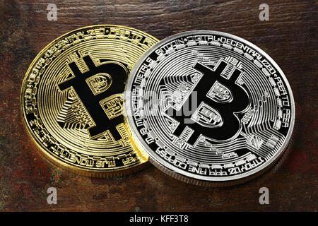 golden and silver bitcoins on wooden background - Stock Photo