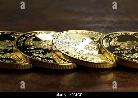 Bitcoin in a row of 1 ounce American gold eagle bullion coins - Stock Photo