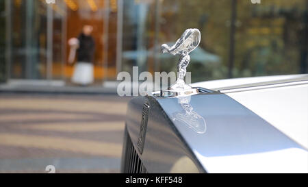 Spirit of Ecstacy or Emily logo on the hood of a rolls Royce. and bride the background. Emmy or Spirit of Ecstacy, - Stock Photo