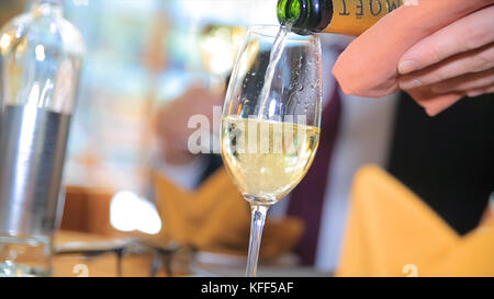 Pour the champagne into a glass. Bartender pouring champagne into glass, close-up. Champagne pouring in glass - Stock Photo