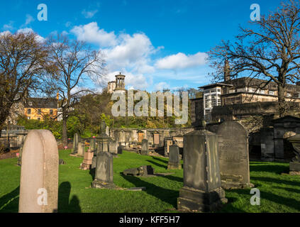 Old gravestones in Old Calton burying ground cemetery Edinburgh, Scotland and view to Calton Hill, with Nelson column - Stock Photo