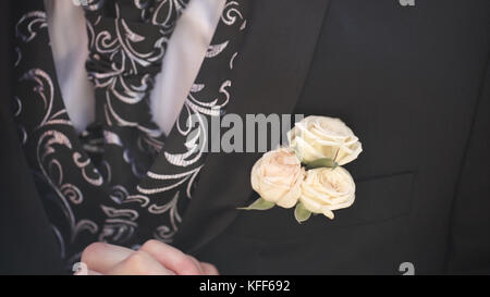 Carnation flower in a pocket. the flower in jacket pocket. pin with decorative white flowers pinned on the groom's - Stock Photo