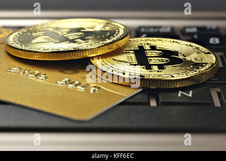 bitcoins and credit card on a laptop keyboard - Stock Photo