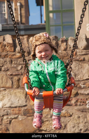 Smiling baby girl playing in children´s playground on Portobello Beach Promenade in capital of Scotland, in Edinburgh. - Stock Photo