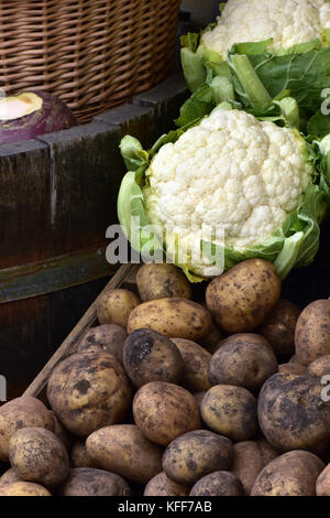 A cauliflower and some potatoes next to a wicker basket on sale outside of a greengrocers shop. Fresh produce from - Stock Photo