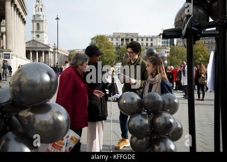 London, UK. 28th Oct, 2017. Tow young people explain the idea of the movement at two old women, one of them is blind. - Stock Photo