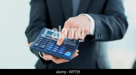 Businessman holding calculator. pressing button - Stock Photo