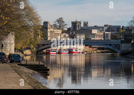 Autumn sun & beautiful riverside setting by gently flowing River Ouse, Lendal Bridge, boats moored & historic York - Stock Photo