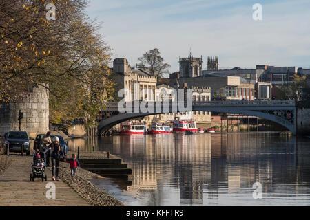 People in York walk in autumn sun & enjoy beautiful riverside setting by River Ouse, Lendal Bridge & historic York - Stock Photo