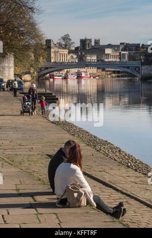 People in York relax in Autumn sun & enjoy beautiful riverside setting by River Ouse, Lendal Bridge & historic York - Stock Photo