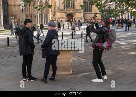 Man takes photo with phone as tourists stand in York centre piazza by model of Minster area, cathedral & people - Stock Photo