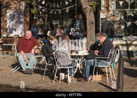 Tables & chairs outside a cafe & people on holiday enjoying autumn sun, sitting, relaxing & having refreshments - Stock Photo