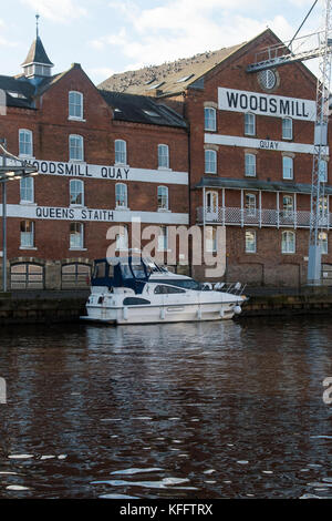 View across River Ouse to pleasure cruiser moored by Woodsmill Quay, an old industrial mill building converted to - Stock Photo