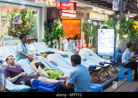 Tourists getting massages just off Khao San Road, Bangkok - Stock Photo