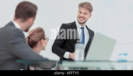 Successful business man in suit at the office leading a group - Stock Photo