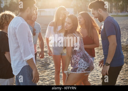 Portrait of group of happy friends partying on beach - Stock Photo