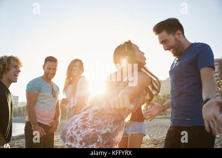 Portrait of couple dancing on beach partying with friends - Stock Photo