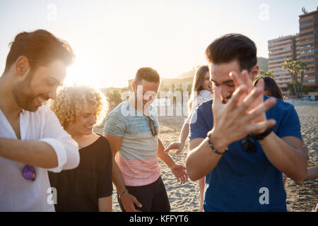 Portrait of happy man dancing on beach with friends clapping his hands - Stock Photo