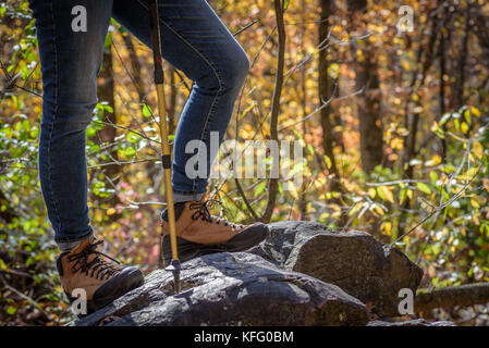 Woman in hiking boots standing on top of large rock at Devil's Lake State Park Wisconsin - Stock Photo