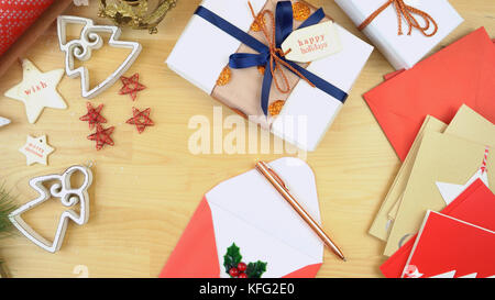 Wrapping gifts and writing Christmas cards overhead. - Stock Photo