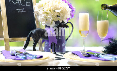 Horse racing Racing Day Luncheon fine dining table setting with small black fascinator hat, decorations and champagne, - Stock Photo