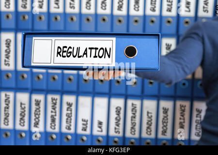 Regulation Business Concept. Young man holding ring binder. - Stock Photo