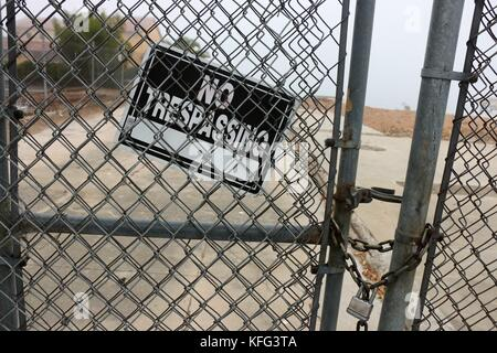 No Trespassing sign on a chain link fence. - Stock Photo