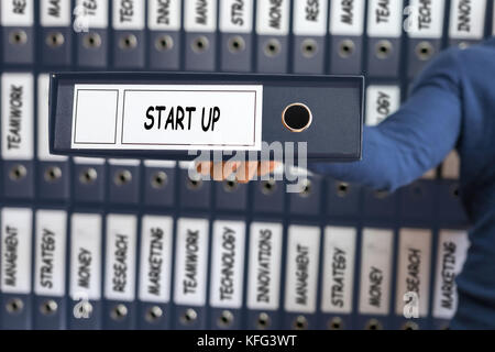 Start Up Concept. Business concept. Young man holding ring binder. - Stock Photo