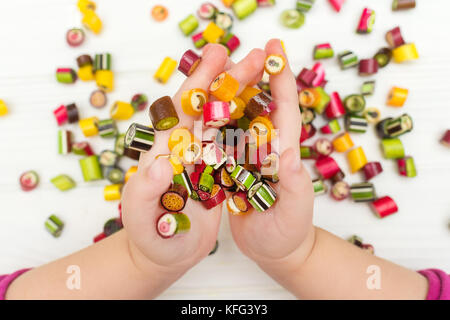 A colored caramel candies in child hands - Stock Photo