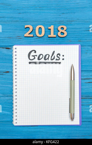 Notebook with new years goals for 2018 with a pen and numbers 2018 on a blue wooden table - Stock Photo
