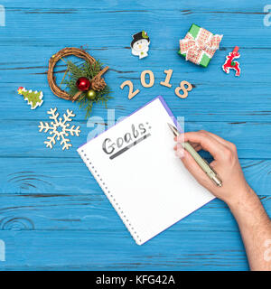 notebook with GOALS text and man's hand holding pen above with numbers 2018 and new year ornaments - Stock Photo