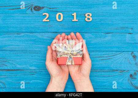 Woman's hands holding gift box near numbers 2018 on blue old table - Stock Photo
