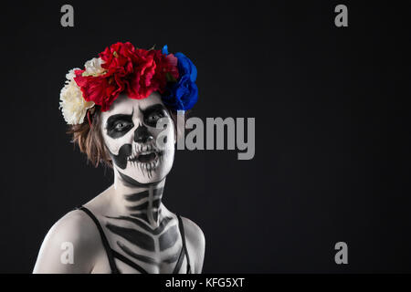 Halloween make up. Portrait of a horrible scary zombie woman wreath over black background. Halloween - Stock Photo