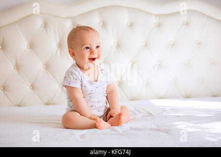 Adorable baby boy in white sunny bedroom. Newborn child relaxing in bed. Nursery for young children. Textile and - Stock Photo