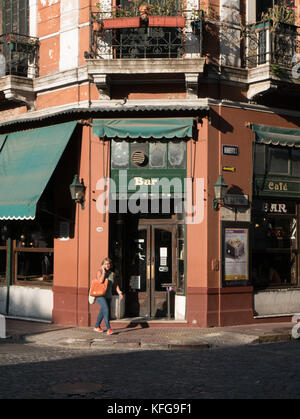 Woman walking on sidewalk in late afternoon talking on cell phone in front of old green and brown bar in San Telmo - Stock Photo