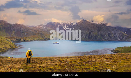 Passengers returning to their Antarctic expedition ship anchored in a calm bay after exploring the dramatic scenery - Stock Photo