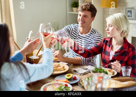 Friends Clinking Glasses at Dinner Party - Stock Photo
