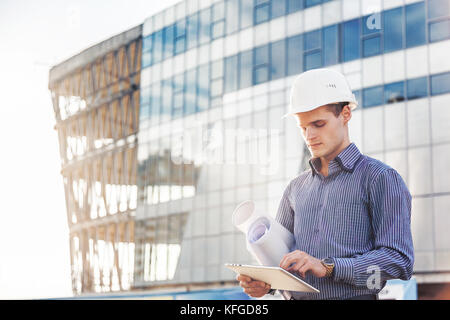 Portrait of confident young architect or chief engineer uses digital tablet at the construction site - Stock Photo