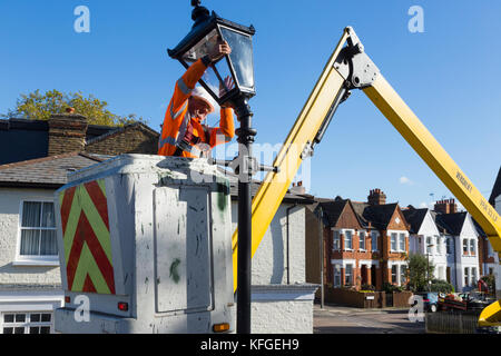 Team of lighting contractors fitting a Heritage street lamp / street lamp / lamppost / cast iron lighting column - Stock Photo