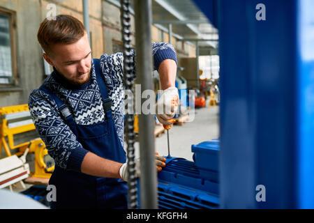 Repairman Fixing Machine Units at Factory - Stock Photo