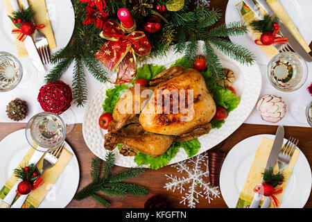 Baked turkey or chicken. The Christmas table is served with a turkey, decorated with bright tinsel and candles. - Stock Photo